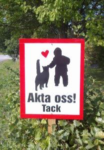 """liikennemerkki jossa kissa, lapsi ja teksti """"Akta oss, tack"""""""